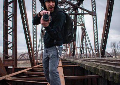 justin hallberg with camera on a bridge