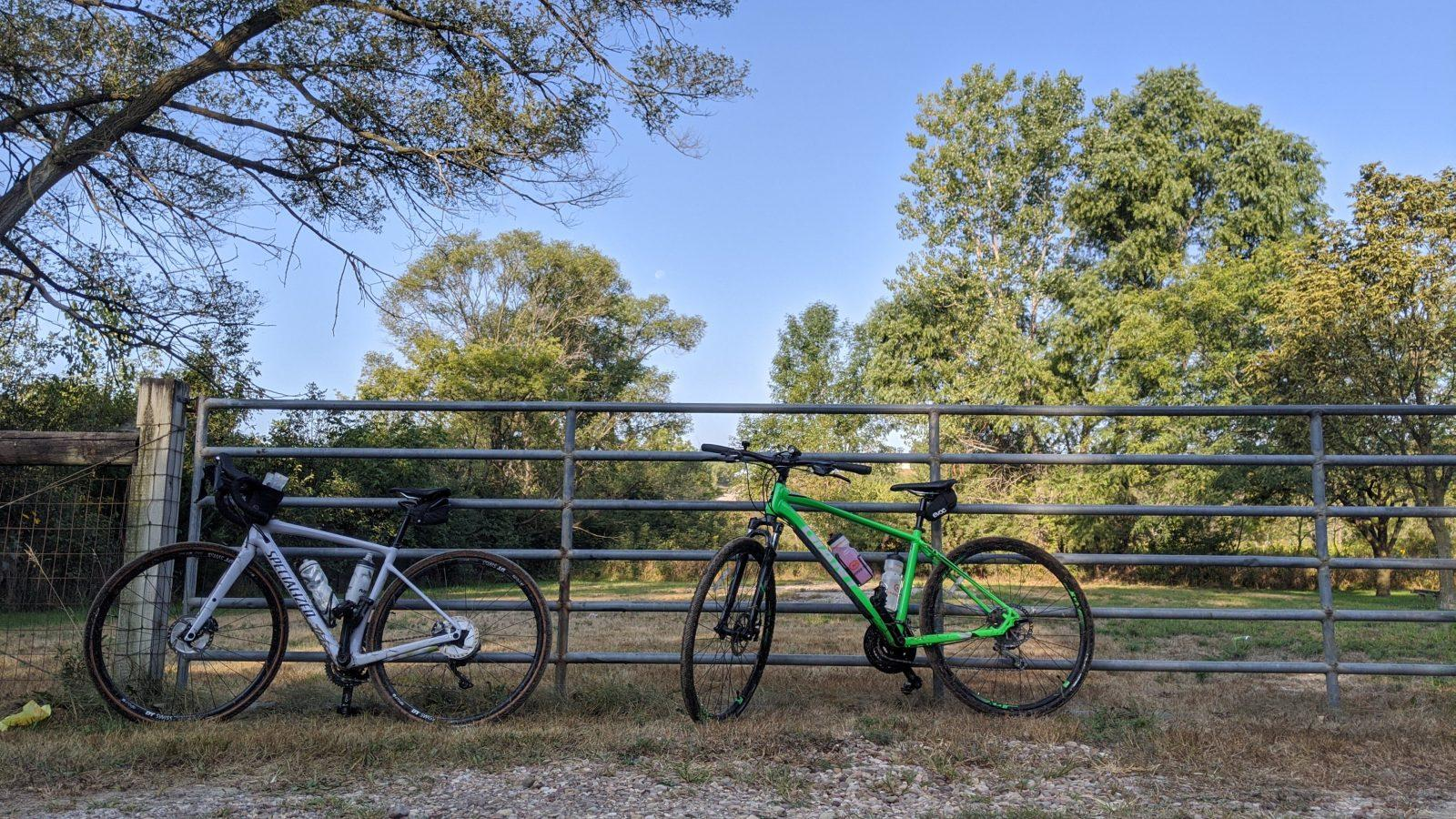 a gravel bike and a crossover bike standing against an iron gate at lake cunningham in omaha, nebraska