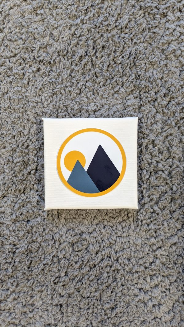 monolith trail co brandmark circle sticker on top of a small square canvas on gray carpet
