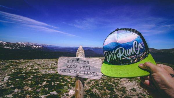 dirt run co trucker hat with a 12,000 foot mountain sign behind it