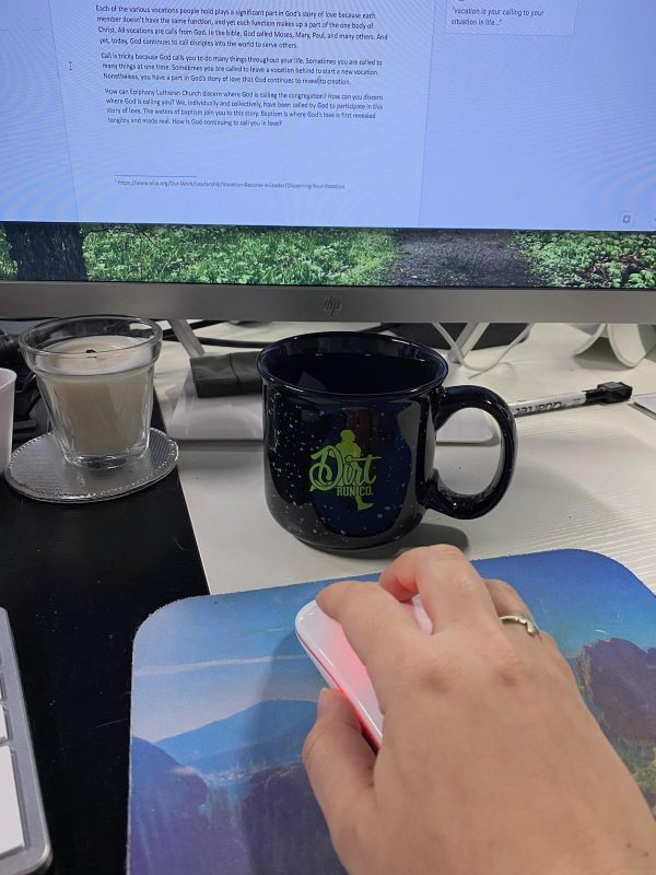 dirt run co mug next to a macbook with a candle and dirt run co mousepad