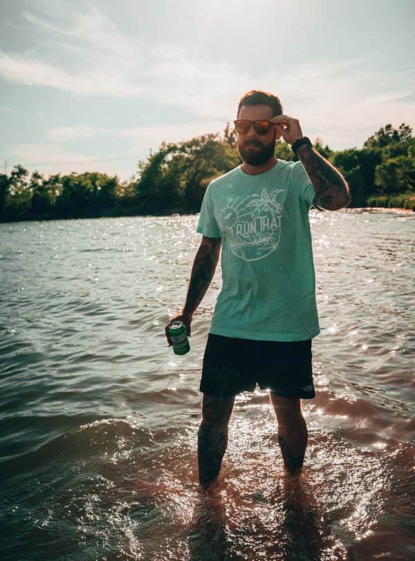 man standing in a lake holding his goodr glasses and a beer wearing i'd run that tee - beachy