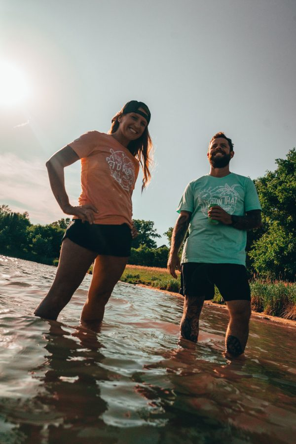woman and man standing in a lake holding and a beer wearing i'd run that tee - beachy