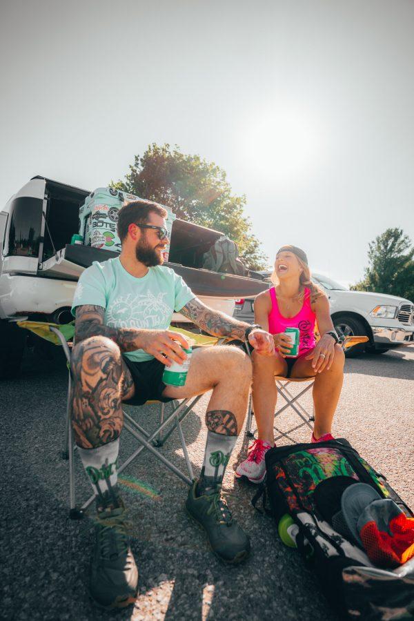 man and woman tailgaiting wearing dirt run co shirts