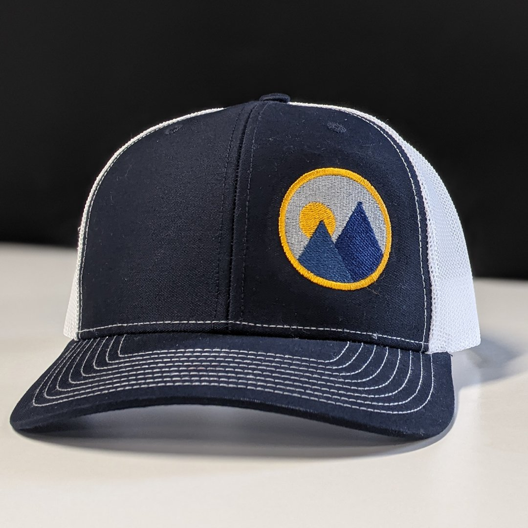 product shot of monolith trail co trucker hat in navy with the brandmark on one panel