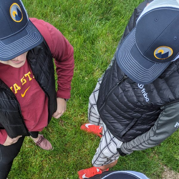 aerial view of monolith trail co trucker hats on a male and female