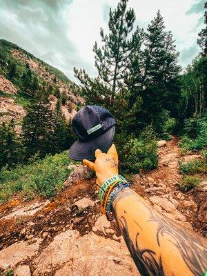 man's arm holding a dirt run co trucker hat in the mountains of colorado